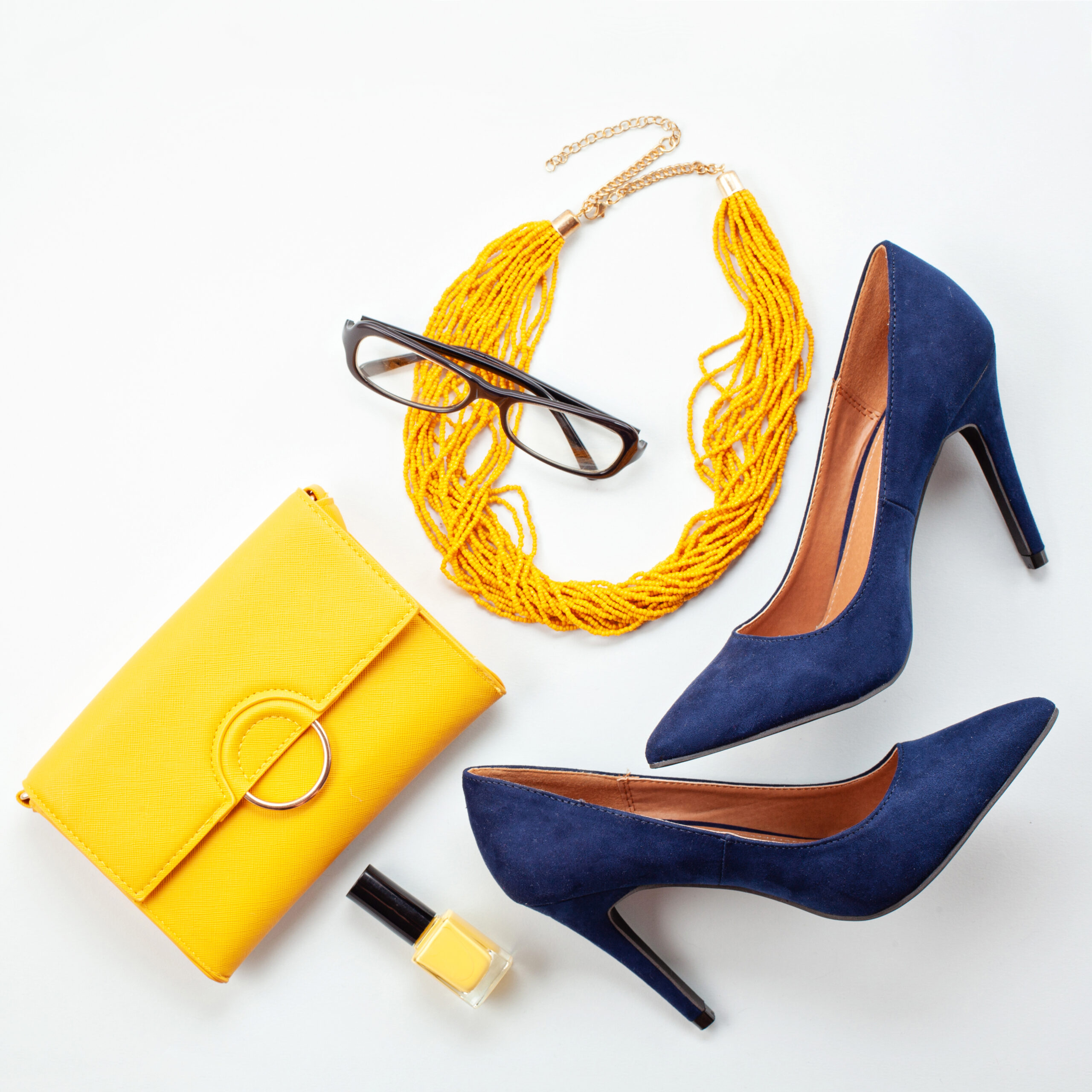 Bright yellow accessories and blue shoes for girls and women. Urban fashion, beauty and fashion blog concept
